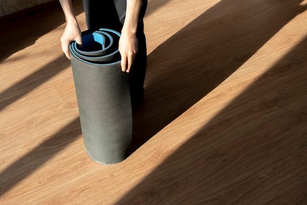 Mężczyzna toczący matę do jogi po podłodze podczas treningu jogi
