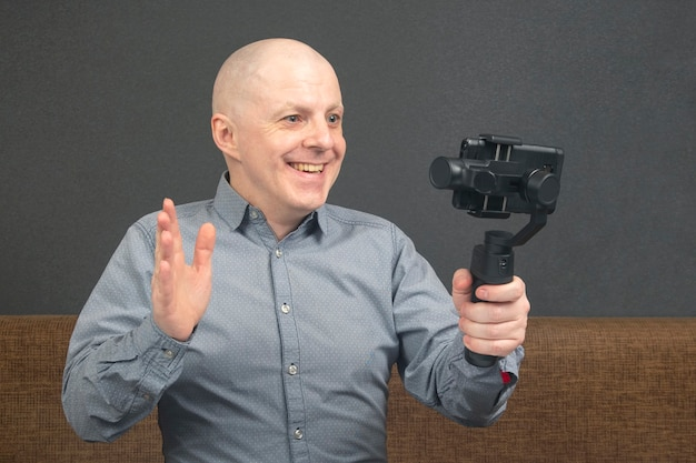 Mężczyzna transmituje domowe wideo do smartfona ze stabilizatorem