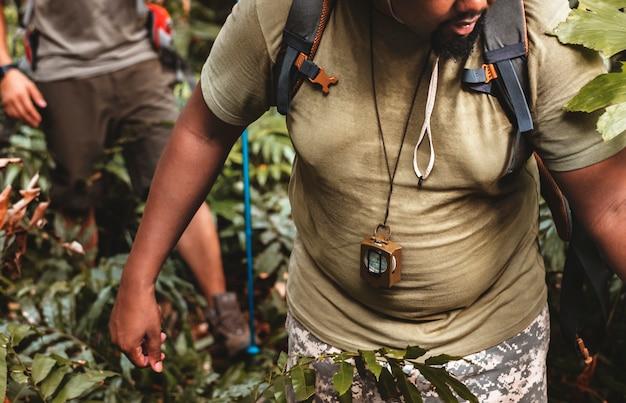 Mężczyzna trekking w lesie z przyjaciółmi