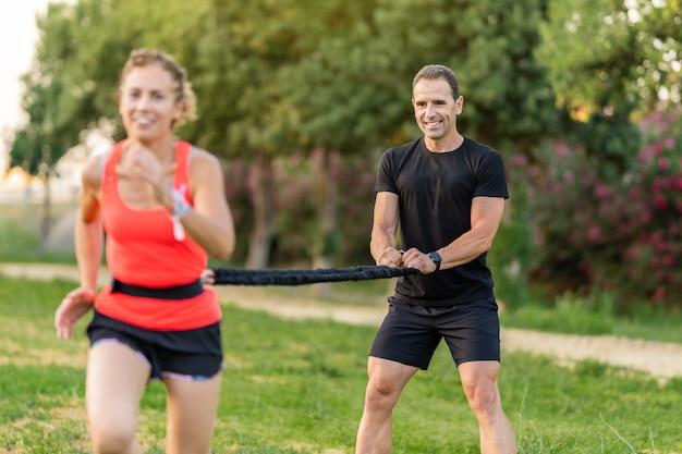 Mężczyzna trener osobisty ćwiczy z kobietą i pomaga jej w treningu.