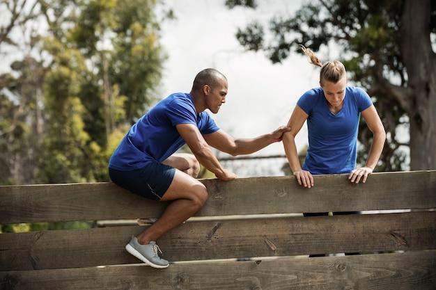 Mężczyzna trener pomaga kobiecie wspiąć się na drewnianą ścianę