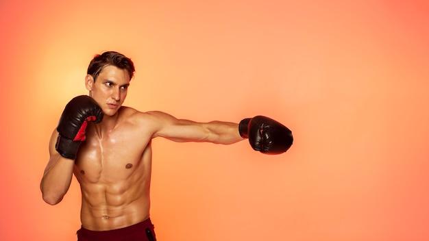 Mężczyzna trenujący w rękawicach bokserskich, średni strzał