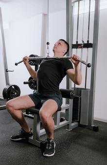 Mężczyzna trenuje na siłowni na symulatorze, wykonuje ćwiczenia dla różnych grup mięśni. pragnienie zaspokojenia głodu, zdrowe, wysportowane ciało. nowoczesny klub fitness