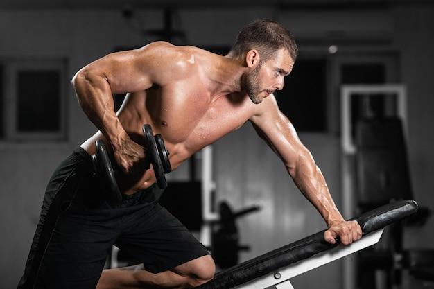 Mężczyzna trenuje na siłowni. sportowy mężczyzna trenuje z hantlami, pompując biceps