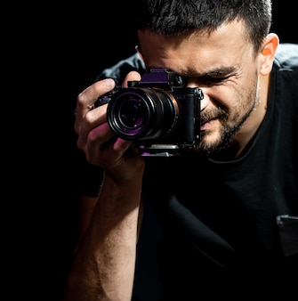 Mężczyzna trzyma aparat i jest przygotowany do fotografowania. fotograf patrzy w wizjer aparatu i robi zdjęcia.