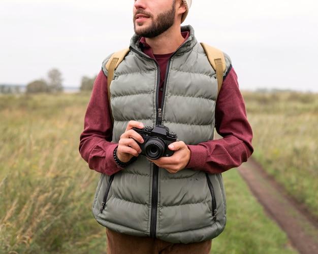 Mężczyzna trzyma aparat w przyrodzie