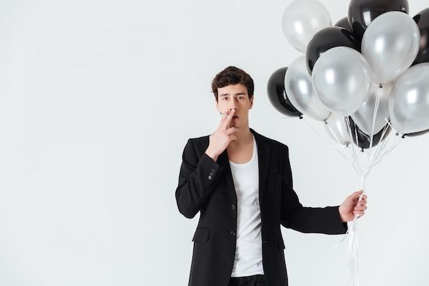 Mężczyzna trzyma balony i palenie papierosów