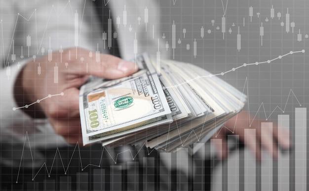 Mężczyzna trzyma banknoty dolara z wykresem wzrostu.