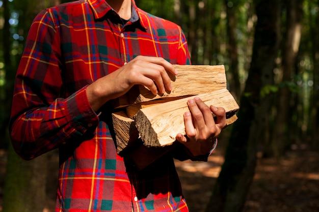 Mężczyzna trzyma bele drewna na ognisko