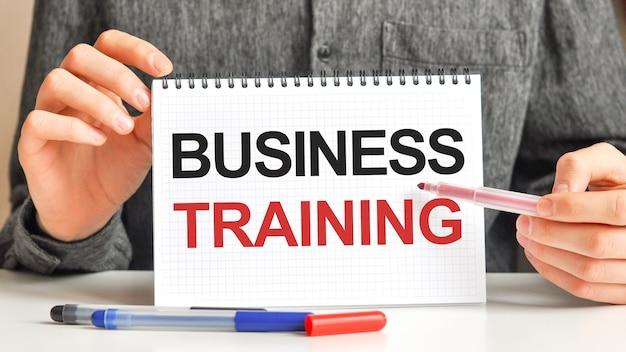 Mężczyzna trzyma białą tabletkę z tekstem szkolenia biznesowe, koncepcja biznesowa.