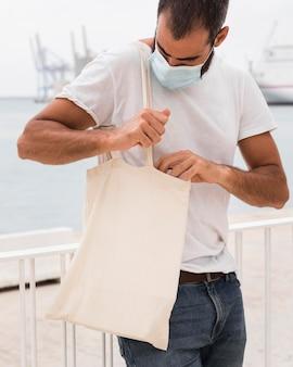 Mężczyzna trzyma białą torbę i ma na sobie maskę medyczną