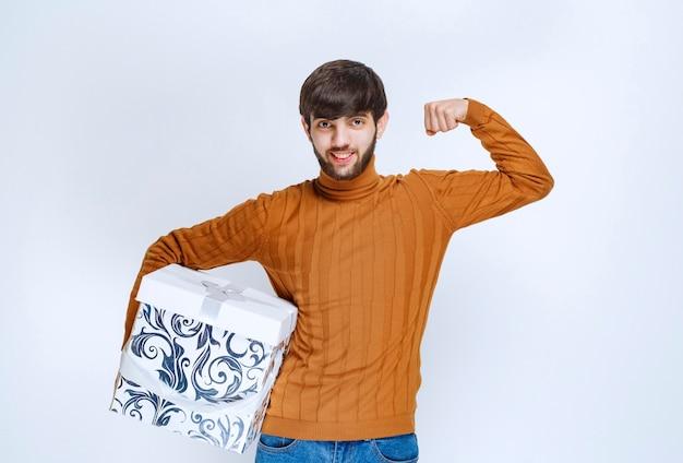Mężczyzna trzyma białe pudełko z niebieskimi wzorami i pokazuje znak satysfakcji.