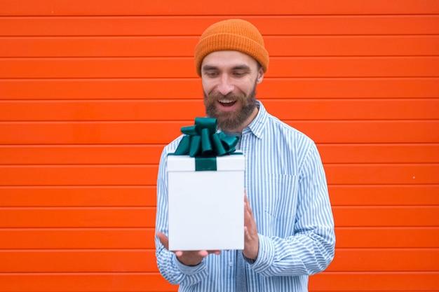 Mężczyzna trzyma białe pudełko z zieloną kokardką