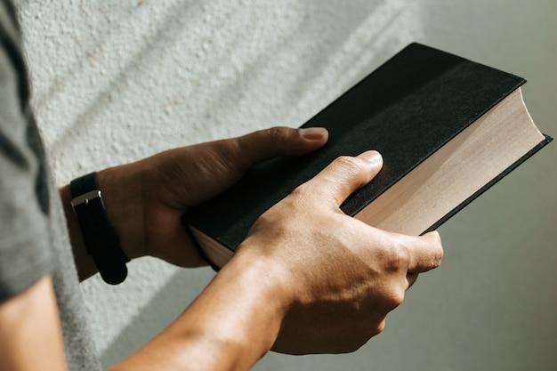 Mężczyzna trzyma biblię w jego ręce. wierzący pojęcie