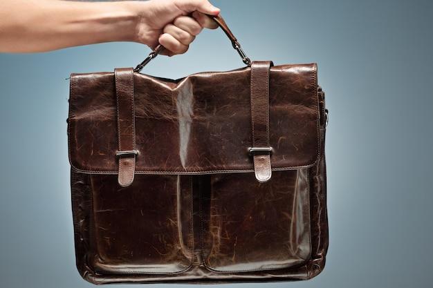 Mężczyzna trzyma brązową skórzaną torbę podróżną