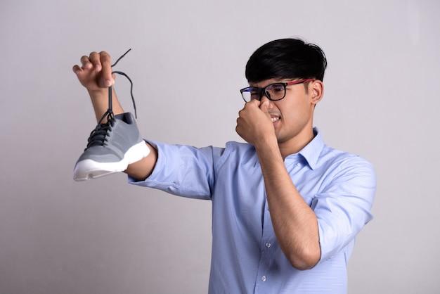 Mężczyzna trzyma brudny śmierdzący but z wyrazem obrzydzenia. pojęcie opieki zdrowotnej.