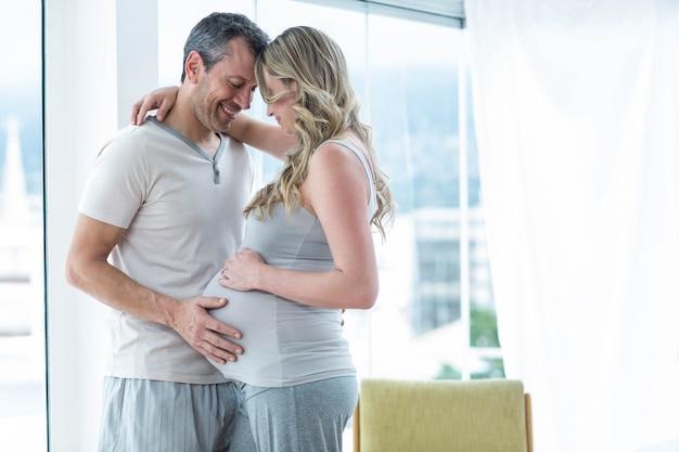 Mężczyzna trzyma brzuch kobiety w ciąży w sypialni