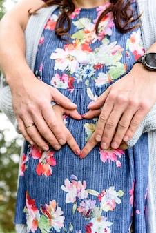 Mężczyzna trzyma brzuch swojej ciężarnej żony. kobieta w ciąży i kochający mąż przytulanie brzuch.