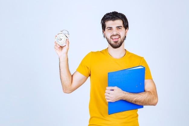 Mężczyzna trzyma budzik i niebieską teczkę.