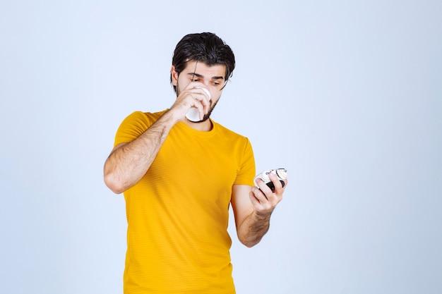 Mężczyzna trzyma budzik i pije kawę.