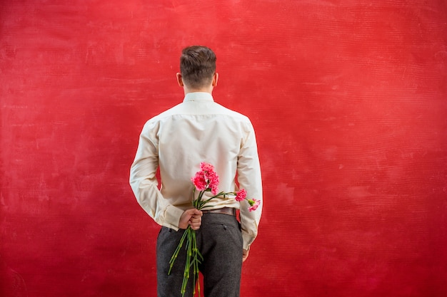 Mężczyzna trzyma bukiet goździków za plecami na czerwonym studio
