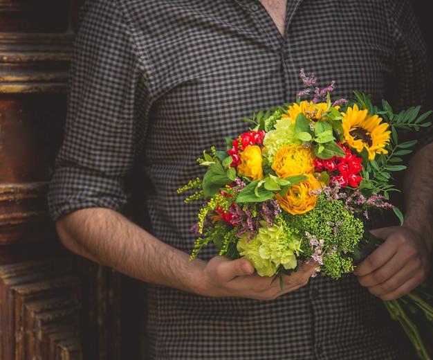 Mężczyzna trzyma bukiet kwiatów jesiennego słońca inspirowane