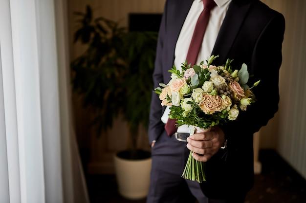 Mężczyzna trzyma bukiet ślubny