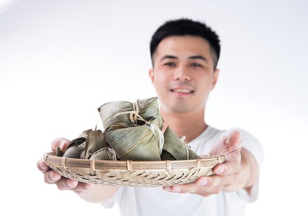 Mężczyzna trzyma bukiet zongzi (pierogów ryżowych) na festiwal smoczych łodzi