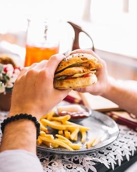 Mężczyzna trzyma burgera z kurczaka podawane z frytkami i sosem