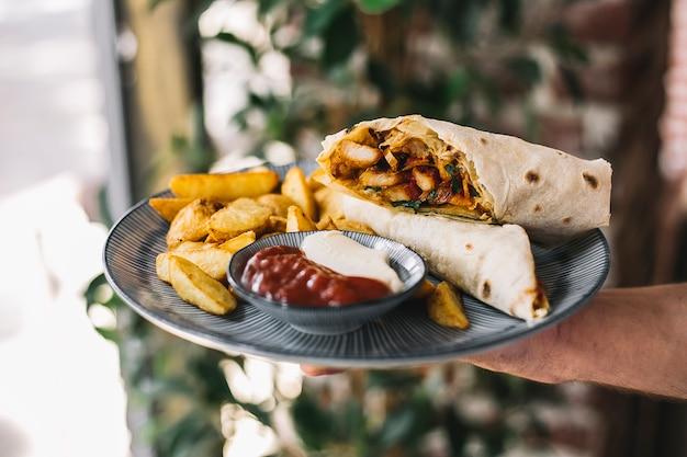 Mężczyzna trzyma burrito z kurczaka podawane z frytkami majonezem i keczupem