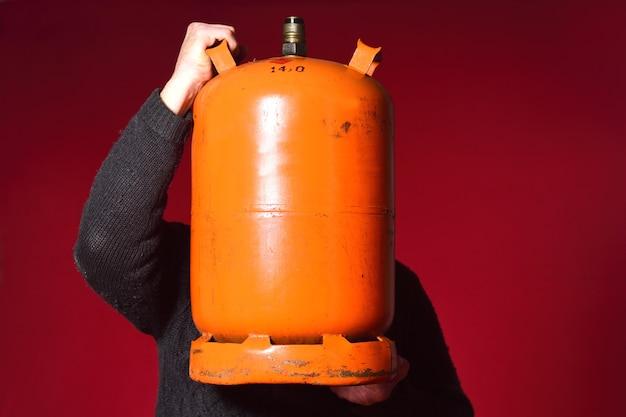 Mężczyzna trzyma butelkę butanu na czerwonym tle