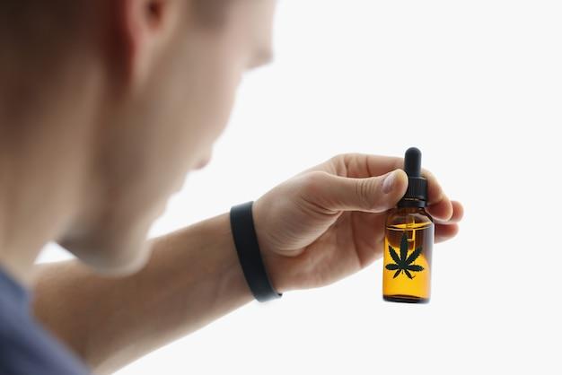 Mężczyzna trzyma butelkę ekstraktu marihuany w jego ręce zbliżenie. nielegalny zakup koncepcji narkotyków