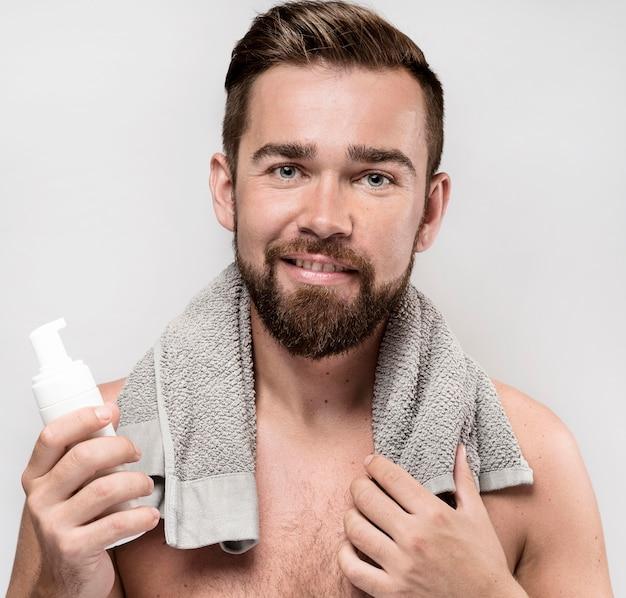 Mężczyzna trzyma butelkę kremu do golenia