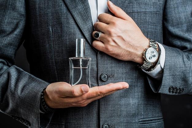 Mężczyzna trzyma butelkę perfum. do ręki zegarek w garniturze. butelka perfum lub wody kolońskiej i perfumy, kosmetyki, butelka wody kolońskiej zapachowej, woda kolońska dla mężczyzn.