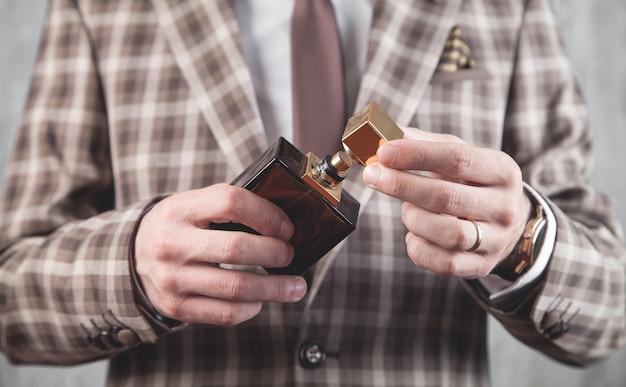 Mężczyzna trzyma butelkę perfum.