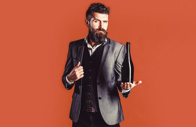 Mężczyzna trzyma butelkę wina. brodaty mężczyzna z butelką szampana i szkła.