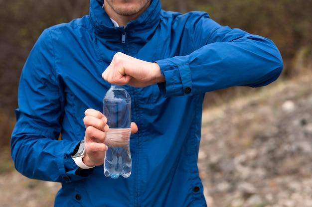 Mężczyzna trzyma butelkę wody w przyrodzie