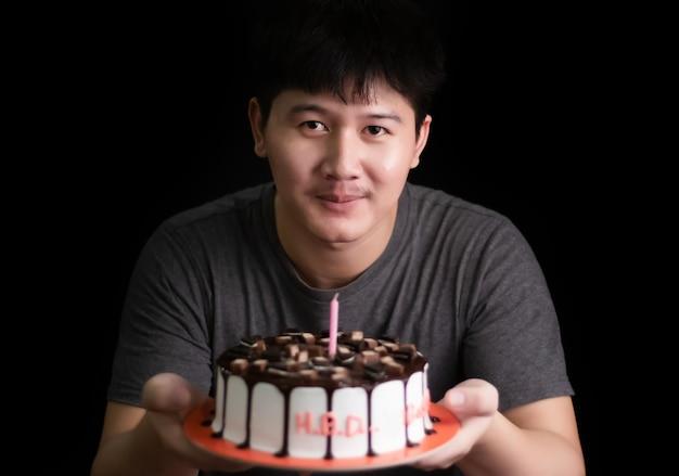 Mężczyzna trzyma ciasto czekoladowe na rustykalnym drewnianym stole na czarnym tle