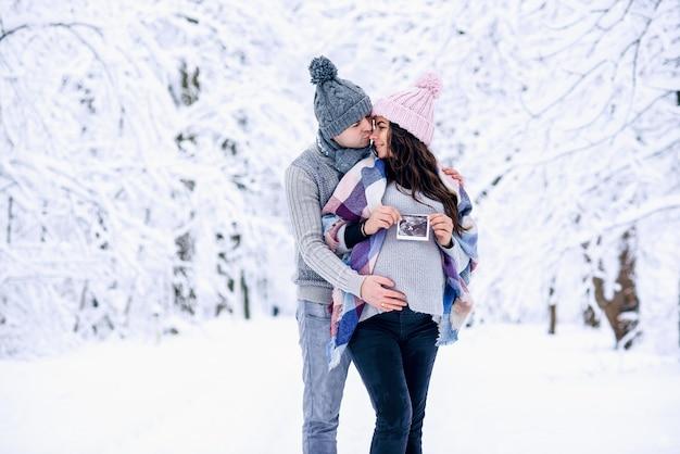 Mężczyzna trzyma ciężarny brzuch żony i całuje ją delikatnie w nos w śnieżnym zimowym parku