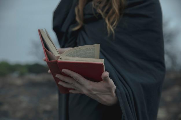 Mężczyzna trzyma czerwoną książkę na zewnątrz