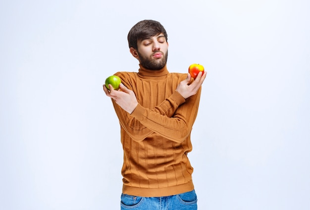 Mężczyzna trzyma czerwone i zielone jabłka w obu rękach.