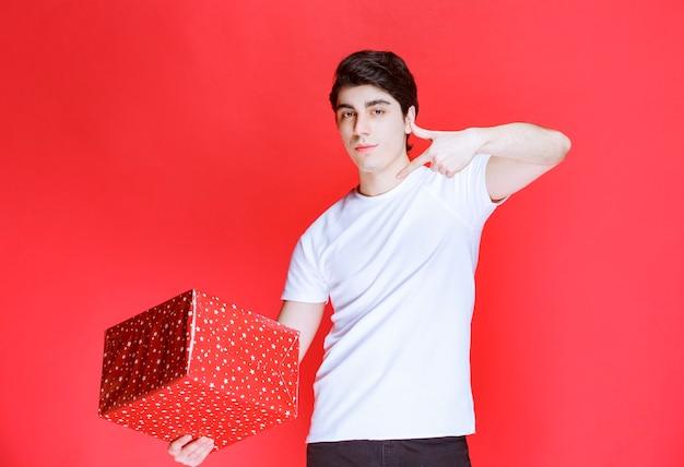 Mężczyzna trzyma czerwone pudełko i wskazuje na nie