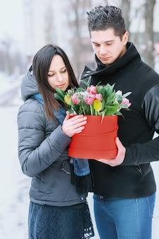 Mężczyzna trzyma czerwone pudełko z pięknym bukietem kwitnących różowych, żółtych i białych tulipanów i białych chryzantem z zielonymi liśćmi, na zewnątrz