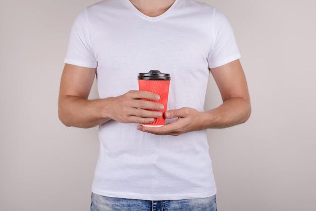 Mężczyzna trzyma czerwony kubek na na białym tle szarym tle