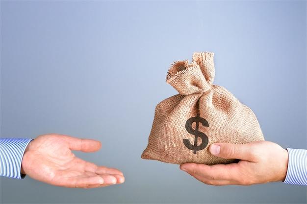 Mężczyzna trzyma, daje w ręku torbę pieniędzy jak bonus. biznesmena mienia torba pieniądze w ręce oferuje łapówkę z kopii przestrzenią. koncepcja torby gotówkowej.