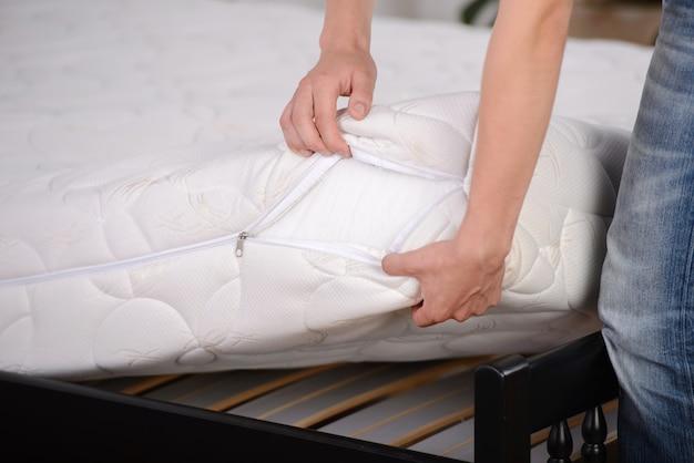 Mężczyzna trzyma demonstracje jakości materac w sypialni.