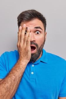 Mężczyzna trzyma dłoń na twarzy, opada szczęka, widzi coś okropnego, ubranego w casualową niebieską koszulkę wyizolowaną na szaro