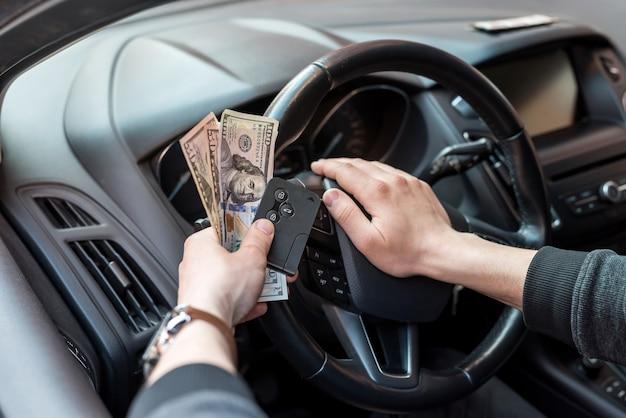 Mężczyzna trzyma dolara i kluczyk do samochodu, aby zapłacić czynsz lub łapówkę
