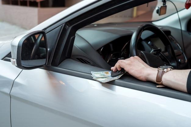 Mężczyzna trzyma dolara i kluczyk do samochodu na opłacenie czynszu lub łapówkę finansową