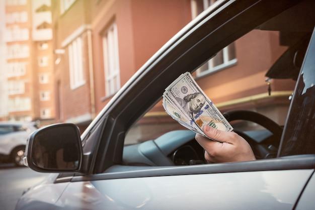 Mężczyzna trzyma dolarów siedzi w samochodzie. kupić lub wypożyczyć, przekupić